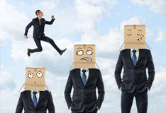 Small businessman jumping over three men in suits who are wearing carton boxes with painted faces. Stock Photo