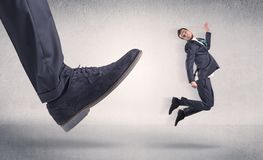 Small businessman kicked by big shoe. Small businessman deported from workplace by his bossn stock images