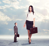 Small businessman looking up at on high walking Stock Photo