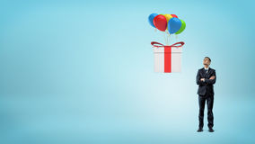 A small businessman looking up at a large gift box flying away on colorful balloons. Royalty Free Stock Images