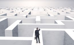 Small businessman in a middle of a maze royalty free stock photo