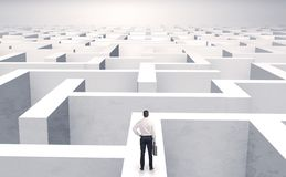 Small businessman in a middle of a maze. Small businessman in a middle of a huge maze royalty free stock photography