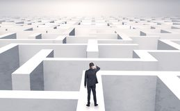 Small businessman in a middle of a maze. Small businessman in a middle of a huge maze stock photos