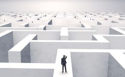 Small businessman in a middle of a maze. Small businessman in a middle of a huge mazen royalty free stock image