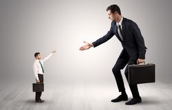 Small businessman pointing to a giant businessman stock photo