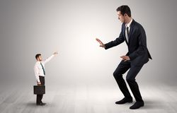 Small businessman pointing to a giant businessman. Small businessman in shirt pointing to an afraid businessman stock image