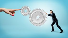 A small businessman pushes at a large gear interlocked with a small one while a female finger stops their movement. Manufacturing business. Industrial royalty free stock photo