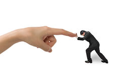 Small businessman pushing against big hand forefinger. Isolated on white stock image