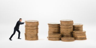 Small businessman pushing a stack of golden coins to another stacks Royalty Free Stock Photo