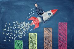 A small businessman rides a rocket leaving a tail of dollar bills over a statistic chart. stock illustration