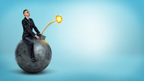 A small businessman riding a big round bomb with a lit fuse on blue background. Work under pressure. Strict deadline. Dangers of tardiness Stock Photos