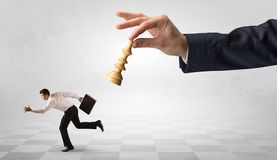 Small businessman running away from big hand with chessman concept. Small frail businessman with suitcase running away from big hand with chessman conceptn Stock Photo
