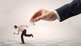 Small businessman running away from big hand with chessman concept royalty free stock photos