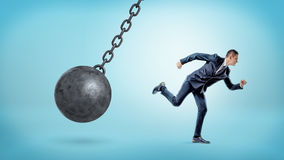 A small businessman running away from a giant black wrecking ball on a chain. Business trouble. Leaving problems behind. Run away from crisis Stock Photos