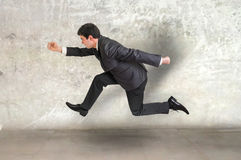 Small businessman running away Royalty Free Stock Image
