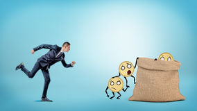 A small businessman running to a large full sack where many coins with arms and legs are getting in. Royalty Free Stock Image