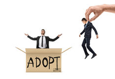 Small businessman sitting in box marked `Adopt` and looking up, while giant hand brings another man Stock Photos