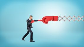 A small businessman in sport gloves punches a giant red boxing glove on a metal scissor arm. Unfair competition. Business trouble. Hard-earned profit Royalty Free Stock Images