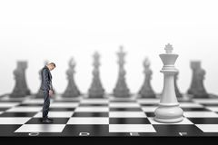 A small businessman stands with his head down in front of a white kind on a large chessboard. royalty free stock photo