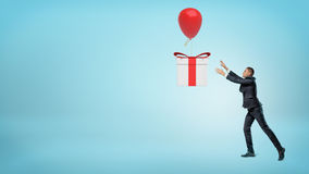 A small businessman trying to catch a big gift box that is flying away on a balloon. Royalty Free Stock Photography