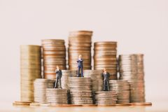 Small businessmans figures standing on coins stack. royalty free stock photo