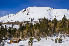 Small Cabin At Base of Snow Covered Mountain Stock Photo