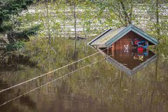 Small cabin floating in the water, tied with a rope. Flooding from the river Tovdalselva in Kristiansand, Norway -. Small cabin floating in the water, tied with Stock Photos