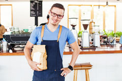 Small cafe owner holding a package of coffee beans Stock Images