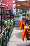 Small cafe with wicker furniture and umbrellas on a bridge Royalty Free Stock Image