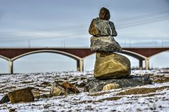 Cairn and bridge on the floodplain. Small cairn on the snow-covered floodplain of the river Waal near Nijmegen, The Netherlands, with city bridge De Oversteen royalty free stock image