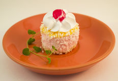 Small cake with cream, cherries and coconut topping Stock Image