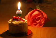 Small  cake with a single candle and rose Stock Images