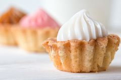 Small cakes and with cream on a white table. Selective focus. stock photo