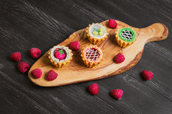 Small cakes petit fours. In the form of baskets with cream and jam on a wooden plank from a tree of olive, worn on a dark black background in rustic style, top Stock Images
