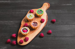Small cakes petit fours. In the form of baskets with cream and jam on a wooden plank from a tree of olive, worn on a dark black background in rustic style, top Royalty Free Stock Image