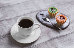Small cakes petit fours tartlets. With jam and cream, ceramic board with a pattern of white lace, with a cup of coffee espresso on a light wooden background Royalty Free Stock Images