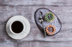 Small cakes petit fours tartlets. With jam and cream, ceramic board with a pattern of white lace, with a cup of coffee espresso on a light wooden background Stock Photography