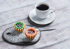 Small cakes petit fours tartlets. With jam and cream, ceramic board with a pattern of white lace, with a cup of coffee espresso on a light wooden background Royalty Free Stock Photos