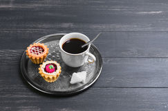 Small cakes petit fours tartlets. With jam and cream, metal tray, with white cup of coffee espresso on darck black wooden background, empty clean place for your Stock Image