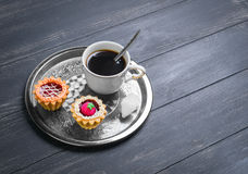 Small cakes petit fours tartlets. With jam and cream, metal tray, with white cup of coffee espresso on darck black wooden background, empty clean place for your Royalty Free Stock Images