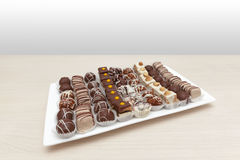 Small cakes on white plate. Wooden table Stock Image