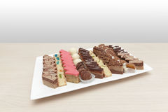 Small cakes on white plate. Wooden table Stock Images