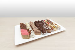 Small cakes on white plate. Wooden table Stock Photos