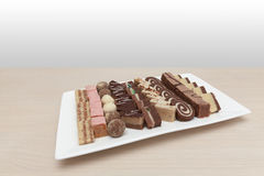 Small cakes on white plate. Wooden table Royalty Free Stock Photos