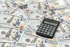 Small calculator on hundred dollar bills Royalty Free Stock Photography