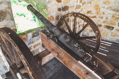 Small caliber cannon at fortress loopholes. Cast-iron cannon on a wooden carriage with large wheels at loopholes of fortress wall Stock Photography