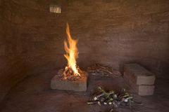 Campfire in primitive adobe hut Stock Image