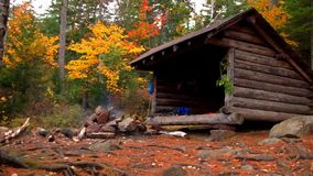 Small campfire burning at log cabin lean to in the Adirondack Mountains. Peak leaf foliage near Lake placid New york stock video