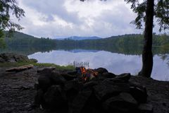 Small Campfire on a misty Lake in the Adirondack Mountains of Upstate New York royalty free stock photos