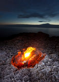 Small campfire on rocky coast at night Stock Photos